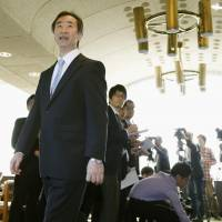 Takaaki Kajita, winner of the Nobel Prize in physics, walks away after speaking with reporters Wednesday morning at the University of Tokyo in the capital's Bunkyo Ward, a day after the announcement of his award. | KYODO