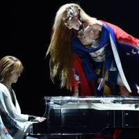 A model wearing a creation by Yoshiki climbs on to his piano during a final show of Mercedes Benz Tokyo Fashion Week. | AFP-JIJI