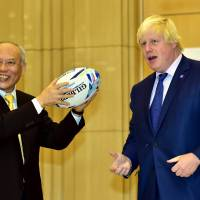 Tokyo Gov. Yoichi Masuzoe receives a rugby ball from London Mayor Boris Johnson after they exchanged documents on the cooperation between both cities at the Tokyo Metropolitan Government office in Tokyo on Wednesday. | AFP-JIJI
