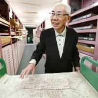 Gen Yamazaki studies a map of the city of Hachioji, west of Tokyo, on which U.S. air raid damage is marked. The map is held at the National Diet Library in Tokyo, where he once worked as a librarian. | KYODO