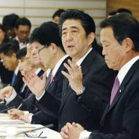 Prime Minister Shinzo Abe address a panel of intellectuals and Cabinet members at his office Thursday during their first meeting to tackle Japan's aging population and low birthrate.   KYODO