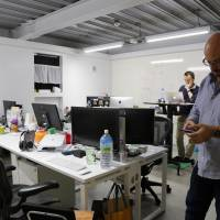 In this Friday, Oct. 16, 2015 photo, Moneytree spokesman Zach Taub (right) checks his mobile phone as other staff members work at their office in Tokyo. | AP