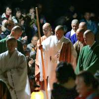 Buddhist monk Kogen Kamahori (center) walks while being assisted at Enryakuji Temple in Otsu, Shiga Prefecture, early Wednesday after completing a nine-day ordeal without eating, drinking, sleeping or lying down, and during which he chanted sutras 100,000 times. | POOL/KYODO
