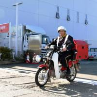 A postman leaves a post office in Aomori on a motor bike Friday morning to deliver identification numbers to residents under the new My Number system. | KYODO