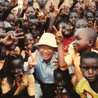 Microbiologist Satoshi Omura, co-winner of the 2015 Nobel Prize in medicine along with William Campbell from Ireland and Youyou Tu from China, strikes a pose with children in Ghana in September 2004. | SATOSHI OMURA/KYODO