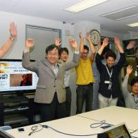 Colleagues of Takaaki Kajita give a banzai cheer Tuesday at their research facility in Hida, Gifu Prefecture, after learning he had won the Nobel Prize. | KYODO