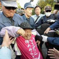 Demonstrators try to block vehicles carrying construction materials for a U.S. Marine Corps replacement base in the Henoko area of Nago, Okinawa Prefecture, on Thursday. | KYODO
