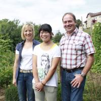 Yuko Taniguchi, an agricultural trainee on a Swiss organic farm, is flanked by her host family, Alois Huber and his wife Silvia, at the farm near Zurich on Aug. 17. | KYODO