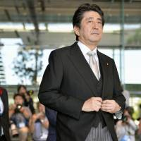 Prime Minister Shinzo Abe leaves the prime minister's office as he heads to the attestation ceremony for Cabinet ministers at the Imperial Palace in Tokyo on Wednesday. | KYODO