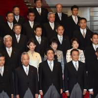 Members of Shinzo Abe's new Cabinet pose for a traditional photo at the prime minister's office in Tokyo's Nagatacho district Wednesday evening. | SATOKO KAWASAKI