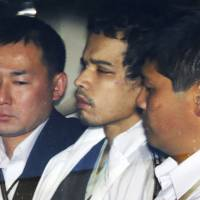 Murder suspect Vayron Jonathan Nakada Ludena is escorted by officers into the Kumagaya Police Station in Saitama Prefecture after his arrest on Oct. 8. | KYODO