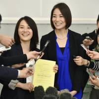 Same-sex partners Hiroko Masuhara (left) and Koyuki Higashi display a piece of paper acknowledging receipt of their application for recognition of their relationship at Tokyo's Shibuya Ward office on Wednesday. It is the first such program nationwide. | KYODO