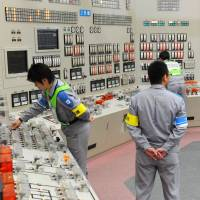 Workers at Kyushu Electric Power Co.'s Sendai nuclear plant in Satsumasendai, Kagoshima Prefecture, carry out procedures to generate and transmit electricity Wednesday after the reactor was restarted earlier this month. | KYODO