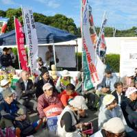 People protest the restart of Kyushu Electric Power Co.'s No. 2 reactor in front of the Sendai nuclear power plant in Kagoshima Prefecture on Thursday. | KYODO