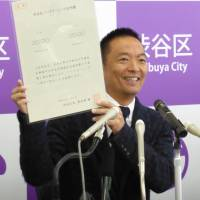 Ken Hasebe, mayor of Tokyo's Shibuya Ward, shows a sample copy of a certificate to recognize same-sex partnerships, which will be issued from Nov. 5, at a news conference Friday. | SHUSUKE MURAI
