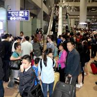 Many arriving tourists are stranded at Kansai International Airport in Osaka Prefecture Thursday evening after trains to the city center were suspended due to strong winds.   KYODO