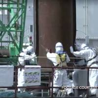 A screenshot of a video shot in late September shows Tepco worker assembling a sea wall at the Fukushima No. 1 nuclear power plant.