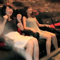 Viewers react to mist and bubbles released in synchronization with a movie at a 4DX theater of United Cinemas Toyosu in Tokyo on July 30. The seats also tilt and shake. | KYODO