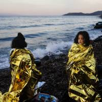 Children stand on a beach wrapped in emergency blankets Wednesday shortly after arriving with other migrants and refugees on the Greek island of Lesbos after crossing the Aegean Sea from Turkey. | AFP-JIJI