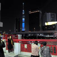 People take photos Saturday in Tokyo's Asakusa district from a vantage point where Sumida Ward's Tokyo Skytree could be seen illuminated in blue. To the right is Asahi Breweries Ltd. headquarters with its distinctive golden flame that sits atop the building. | YOSHIAKI MIURA
