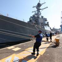 Port workers heave lines as the USS Benfold arrives Monday at Yokosuka, Kanagawa Prefecture. The U.S. Navy said the destroyer carries the most advanced ship-borne ballistic missile tracking and interception system available. | ALASTAIR WANKLYN