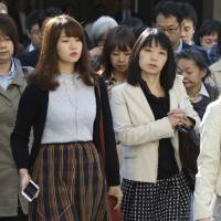 Commuters cross a street during morning rush hour in Tokyo on Monday. Figures show Japan's male-dominated workplaces are accommodating more women, but deep-seated societal forces are keeping the gender gap alive. | AP