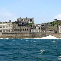 Now called Gunkanjima, Hashima Island appears ominous as tour ferries approach. | TIM HORNYAK