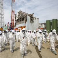 Danger zone: Members of the media and Tepco employees walk in front of the No. 4 reactor building at Fukushima No. 1 nuclear plant in May 2012. The plant was hit by a series of meltdowns following the Great East Japan Earthquake in 2011, and reportage on those meltdowns has been confusing to some in the public. | BLOOMBERG