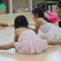 Stretching out: Girls perform some  warm-up exercises before their ballet class of jumping, waving and skipping. DANIELLE DEMETRIOU