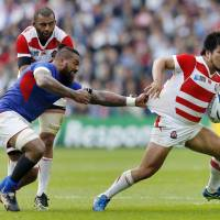 Shota Horie (right) takes Samoa's Faifili Levave for a ride during the two teams' Rubgy World Cup match on Saturday. | REUTERS
