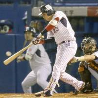 The Swallows' Tetsuto Yamada drives in a first-inning run in Game 4 of the Central League Climax Series final stage on Saturday night at Jingu Stadium. Tokyo Yakult defeated the Yomiuri Giants 3-2 and advanced to the Japan Series. | KYODO