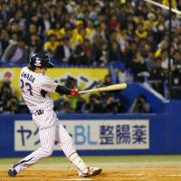 The Swallows' Tetsuto Yamada smacks a two-run, fifth-inning home run against the Hawks in Game 3 of the Japan Series on Tuesday night at Jingu Stadium. Yamada delivered three homers as Tokyo Yakult defeated Fukuoka Softbank 8-4 to cut the Hawks' series lead to 2-1. | KYODO