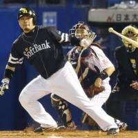 Fukuoka Softbank catcher Toru Hosokawa hits an RBI double on Wednesday night at Jingu Stadium. | KYODO