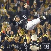 The Hawks give first-year manager Kimiyasu Kudo a traditional doage (victory toss) after clinching the title on Thursday night at Jingu Stadium. | KYODO
