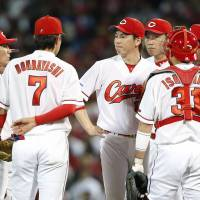 The Carp meet on the mound during the sixth inning on Wednesday in Hiroshima. | KYODO