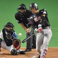 The Marines' Toshiaki Imae hits a bases-clearing double in the second inning against the Fighters in Game 1 of the Pacific League Climax Series final stage on Saturday at Sapporo Dome. Chiba Lotte beat Hokkaido Nippon Ham 9-3. | KYODO