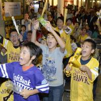 Hawks fans, seen in Fukuoka on Friday night, are thrilled that the team advanced to the Japan Series. | KYODO