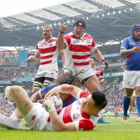 Japan's Kensuke Hatakeyama (center) celebrates a try scored by Akihito Yamada during the Brave Blossoms' 26-5 victory over Samoa at the Rugby World Cup on Saturday in Milton Keynes, England. | GETTY / KYODO