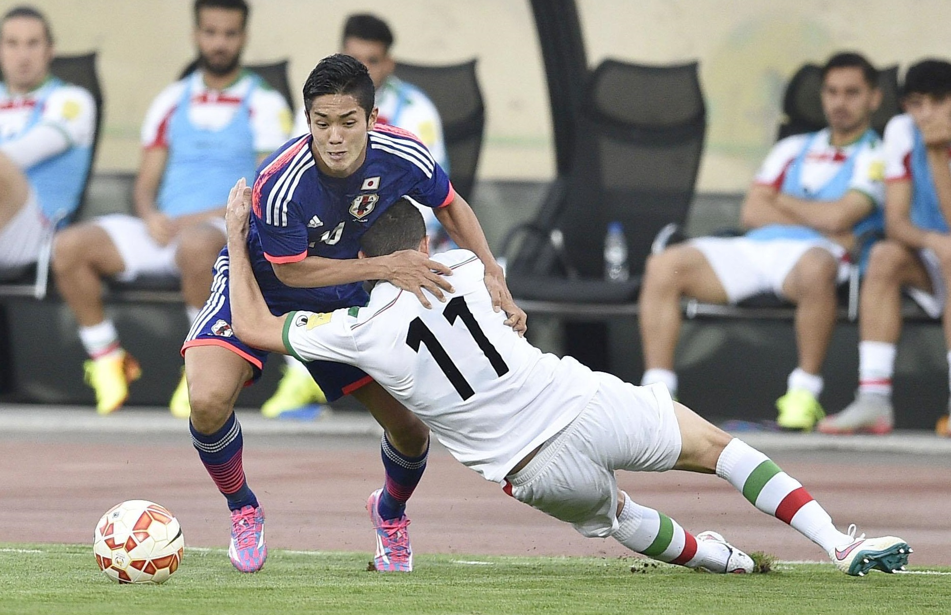 Japan forward Yoshinori Muto tries to get past an Iranian defender during their 1-1 draw in Tehran on Tuesday. | KYODO