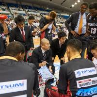 Bench boss Dai Oketani (with clipboard) is calling the shots on a day-to-day basis for the Osaka Evessa, but former Chicago Bulls head coach Bill Cartwright (standing, top right) is providing guidance throughout the season. | OSAKA EVESSA / BJ-LEAGUE