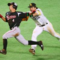 Fukuoka Softbank's Nobuhiro Matsuda tags out Takashi Ogino during the Hawks' 3-2 win over the Marines in Game 1 of the Pacific League Climax Series final stage on Wednesday. | KYODO