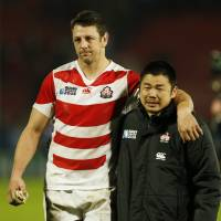 Japan's Luke Thompson puts his arm around teammate Fumiaki Tanaka as they walk off the pitch at Kingsholm on Sunday. | REUTERS