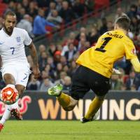 England's Theo Walcott scores past Estonia goalkeeper Mihkel Aksalu in their Euro 2016 qualifier at Wembley Stadium on Friday night. England won 2-0. | REUTERS