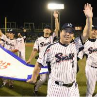 Swallows manager Mitsuru Manaka and his players salute the fans after winning the Central League pennant on Friday night at Jingu Stadium. | KYODO