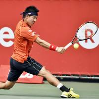 Kei Nishikori plays a shot during his first-round win over Borna Coric at the Japan Open on Monday. | KYODO