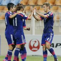Keisuke Honda high-fives his teammates after Japan scored its third goal against Syria in Muscat, Oman, on Thursday. The win pushes Japan to the top of Group E in the Asia qualifying rounds for the 2018 World Cup. | KYODO