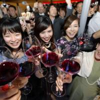 Women raise glasses of Beajolais Nouveau for a toast in a Tokyo event immediately after midnight Wednesday when this year's vintage of the French wine was released. | KYODO