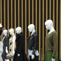 A visitor passes mannequins promoting women's clothes at the Tokyo Fantashion 2015 design event in the city in August. The economy shrank an annualized real 0.8 percent from July to September, its second straight quarterly contraction. | BLOOMBERG