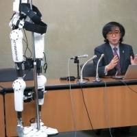 Cyberdyne CEO Yoshiyuki Sankai speaks at a news conference at the health ministry on Wednesday, with the firm's HAL robot suit on display. | KAZUAKI NAGATA