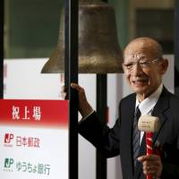 Japan Post Holdings Co. President Taizo Nishimuro prepares to ring a bell marking the company's debut on the Tokyo Stock Exchange on Wednesday. | REUTERS